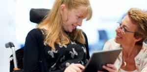 Une jeune fille en fauteuil roulant utilise une tablette numérique. Elle sourit à une femme également souriante.