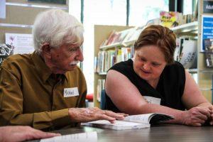 Un homme assez âgé présente un livre à une jeune femme.